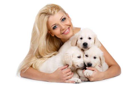 puppy love: Hermosa rubia con un peque�o perrito blanco del retrato Labrador.Studio de mujer hermosa con el pelo largo y rubio y ojos azules, tres peque�os abrazos cachorros de raza labrador blanco, tirado en el suelo en el estudio sobre un fondo blanco