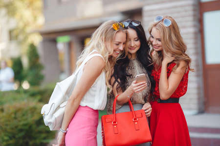 three friends: Three girlfriends looking at pictures on smartphone.Three young beautiful women, two blondes and a brunette, go for a walk together in the city in summer, looking at photos on your Smartphone by lifting up on the forehead sun glasses