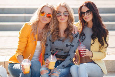 blonde teenage girl: Three smiling women sitting on the steps in the Park.Three beautiful young women, two blondes and a brunette, are walking together in the Park in the summer, sitting on the steps, drinking fruit juice and wearing sun glasses Stock Photo