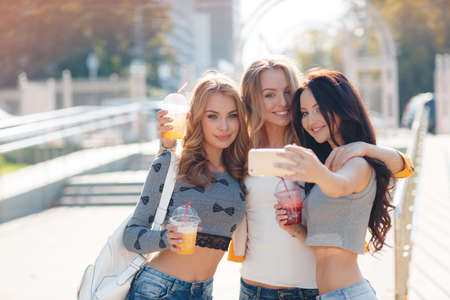 Three beautiful women take off their selfie on smartphone.Three beautiful young women, two blondes and a brunette, are walking together in the Park in summer time, drink fruit juices, smile and take a selfie on your smartphone