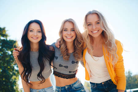 Beautiful young women, three attractive girlfriends with beautiful smiles, two blondes and a brunette, dressed in jeans and short t-shirt, spend time together in the city Park in the summer, posing for a photograph.