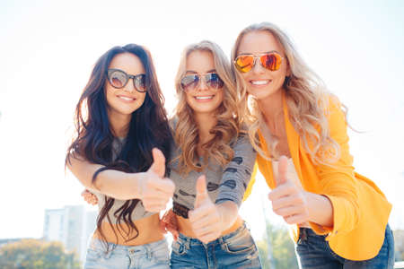 niñas sonriendo: Hermosas mujeres jóvenes, tres novias atractivas con hermosas sonrisas, dos rubias y una morena, vestida con vaqueros y camiseta corta, pasar tiempo juntos en el Parque de la ciudad en el verano, posando para una fotografía. Foto de archivo