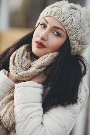 straight jacket: Autumn portrait of a beautiful young woman, brunette with long straight hair and gray eyes, poses for photographer in the fresh air in autumn, dressed in a white jacket, a beige knitted hat and scarf, beautiful makeup