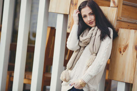 gray eyes: Autumn portrait of a beautiful young woman, brunette with long straight hair and gray eyes, poses for photographer in the fresh air in autumn, dressed in a white coat, beige knitted scarf and jeans, beautiful makeup