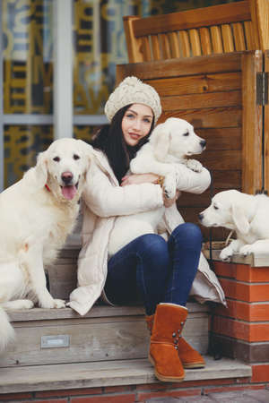 straight jacket: The beautiful girl, the brunette with a long straight hair and gray eyes, in a white jacket and a beige knitted cap, plays on the street in the fall near the house with the favourite dogs of breed the white Labrador Stock Photo