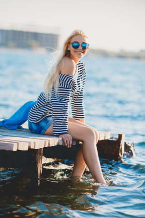 Beautiful Girl in sea style sitting on wooden bridge.Bright beautiful woman, blonde hair, long straight hair, dressed in a striped sailor shirt, blue shorts, sun glasses with blue glasses, sits on a wooden platform on the shore of the blue ocean