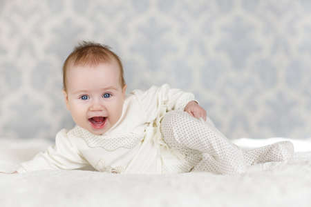 naked child: Portrait of a crawling baby on the bed in her room.Home portrait of happy little baby crawling on white bed dressed in white pants and a white shirt, gray huge eyes, fluffy hair and a satisfied smile Stock Photo