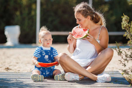 gray eyes: A young mother, brunette with gray eyes and curly hair, with his young son dressed in a striped shirt and blue overalls, summer in the city Park, enjoying the sweet, ripe, red watermelon, sitting on a wooden platform
