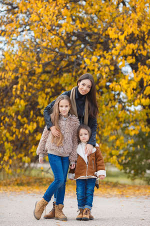 september 2: Three beautiful girls of different ages, eastern appearance, brunette with brown eyes and long hair, cute smile, the three happy sisters relax and have fun together outdoors in yellow autumn park