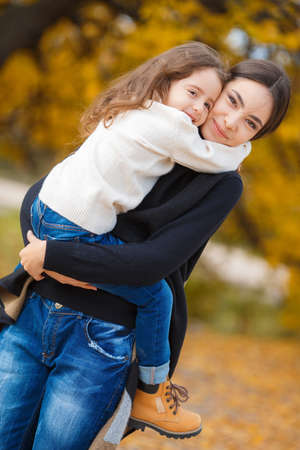 two girls hugging: A beautiful young woman of Oriental appearance, brown hair, brown eyes and long straight hair, spends time with his daughter, a girl with brunette curly hair, blue jeans, outdoors in Park in autumn, among the yellow trees