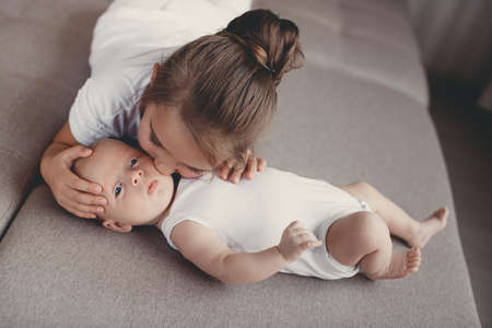 five years old: A little girl five years old, a brunette, dressed in a white shirt and white pants, spends time together with her newborn brother, three-month-old boy, dressed in a white t-shirt and white panties, at home in the bedroom Stock Photo