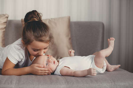 A little girl five years old, a brunette, dressed in a white shirt and white pants, spends time together with her newborn brother, three-month-old boy, dressed in a white t-shirt and white panties, at home in the bedroom Stock fotó