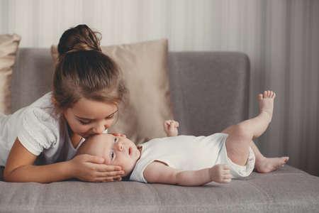 Ein kleines Mädchen fünf Jahre alt sind, eine Brünette, in einem weißen Hemd und weißen Hosen gekleidet, verbringt Zeit zusammen mit ihrem neugeborenen Bruder, drei Monate alten Jungen, in einem weißen T-Shirt und weißen Höschen bekleidet, zu Hause im Schlafzimmer