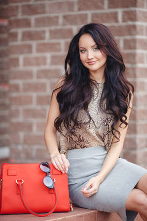 A beautiful young woman, long thick brown hair, gray-green eyes, light makeup and a nice smile, spends time in the city in the summer, sitting near near the brick wall, dressed in a gray skirt and light brown blouse, red bag and glasses Standard-Bild