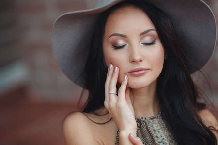 habiliment: Fashionable girl in hat outdoor.Summer portrait of a beautiful woman with long black hair and gray-green eyes, in a dark blouse, sleeveless, beautiful light make-up on his head wearing a hat with large fields of gray
