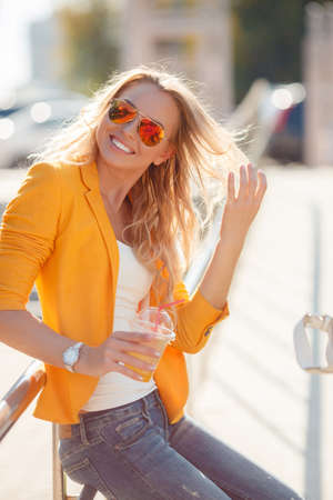 A beautiful young woman, long thick blond hair, mirrored sun glasses, a bright yellow jacket, a nice smile, spends time in the city, standing next to shiny railings with a plastic glass of fruit juice, dressed in blue jeans and a white t -shirt
