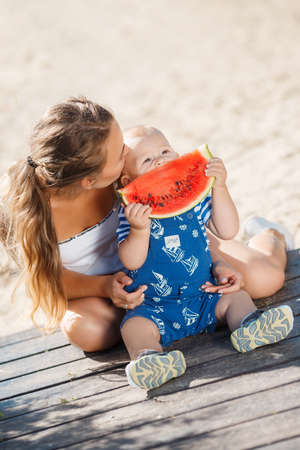 summer fruit: A young mother, brunette with gray eyes and curly hair, with his young son dressed in a striped shirt and blue overalls, summer in the city Park, enjoying the sweet, ripe, red watermelon, sitting on a wooden platform