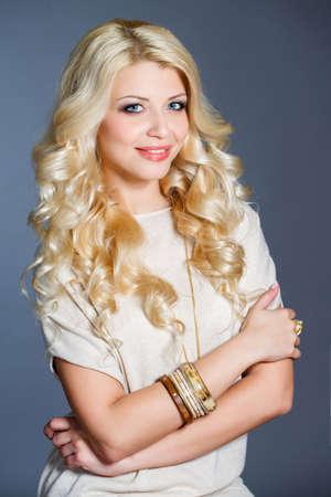 Junge schöne Frau - blond, mit schicken langen lockigen Haar, blaue Augen, trägt einen Ring an den Finger, auf dem Hals - schöne Anhänger, und auf der Hand - Armbänder, in einem beige ärmelloses Kleid gekleidet, isoliert auf grauem Hintergrund.