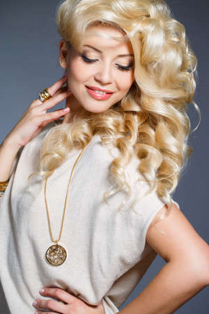 blonde curly hair: Young beautiful woman - blonde, with chic long curly hair, blue eyes, wears a ring on her finger, on the neck - beautiful pendant, and on the hand - bracelets, dressed in a beige sleeveless dress, isolated on gray background.