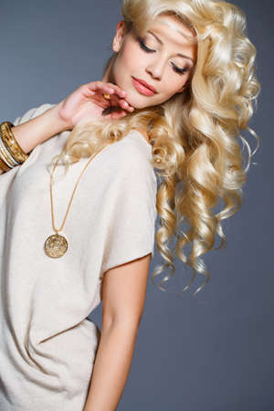 rubia: Joven y bella mujer - rubia, con el pelo rizado largo elegante, ojos azules, lleva un anillo en su dedo, en el cuello - colgante hermoso, y en la mano - pulseras, vestidos con un vestido sin mangas de color beige, aislado sobre fondo gris.