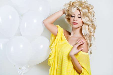 Young beautiful woman - blonde, with chic long curly hair, blue eyes, beautiful make-up and nail polish, wears a ring on his finger and his ears, beautiful earrings, yellow sleeveless dress, isolated on light gray background.