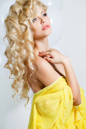 sleeveless dress: Young beautiful woman - blonde, with chic long curly hair, blue eyes, beautiful make-up and nail polish, wears a ring on his finger and his ears, beautiful earrings, yellow sleeveless dress, isolated on light gray background.