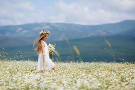Junge schöne Frau, brünett mit langen glatten Haaren, die einen Blumenstrauß der schönen Blumen Feld Gänseblümchen, in ein weißes ärmelloses Kleid gekleidet, trägt den Kopf einen Kranz von weißen Blumen Feld von Gänseblümchen, allein zu Fuß in einer blumigen Feld im Sommer