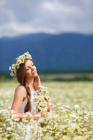 field of daisies: Young beautiful woman brunette with long straight hair, holding a bouquet of beautiful flowers field daisies, dressed in a white sleeveless dress, her head wears a wreath of white flowers field of daisies, walking alone in a flowery field in summer Stock Photo