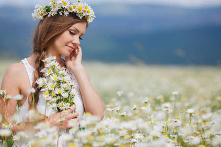 sleeveless dress: Young beautiful woman brunette with long straight hair, holding a bouquet of beautiful flowers field daisies, dressed in a white sleeveless dress, her head wears a wreath of white flowers field of daisies, walking alone in a flowery field in summer Stock Photo