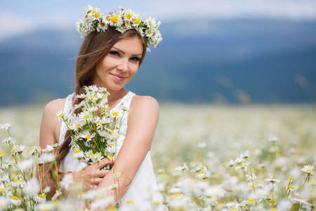 Young beautiful woman brunette with long straight hair, holding a bouquet of beautiful flowers field daisies, dressed in a white sleeveless dress, her head wears a wreath of white flowers field of daisies, walking alone in a flowery field in summer Foto de archivo