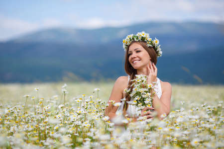 Young beautiful woman brunette with long straight hair, holding a bouquet of beautiful flowers field daisies, dressed in a white sleeveless dress, her head wears a wreath of white flowers field of daisies, walking alone in a flowery field in summer Stok Fotoğraf