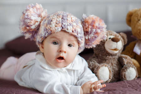 romper: Little girl 3 months old, with brown eyes, dressed in a white cardigan and a pink Romper, knitted beanie with a large bubo, stares at the photographer, lifting his head lying on a purple blanket with plush Teddy bears