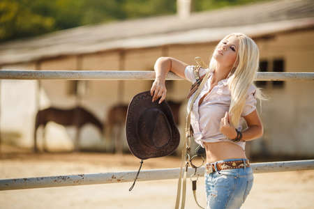 rodeo cowgirl: Young woman with long blonde hair, a big black cowboy hat, flannel shirt and blue jeans, spends time in the summer at the ranch, standing near a wooden fence near the stables