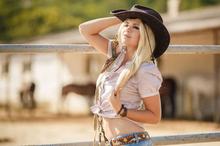 adolescent sexy: Young woman with long blonde hair, a big black cowboy hat, flannel shirt and blue jeans, spends time in the summer at the ranch, standing near a wooden fence near the stables