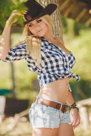 american rodeo: La mujer joven con el pelo largo y rubio, un gran sombrero de vaquero negro, camisa de franela y pantalones cortos de mezclilla azul pasa tiempo en el verano en el rancho, de pie cerca de una valla de madera en el fondo del verdor del verano