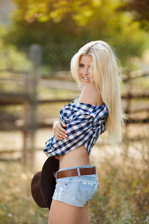 rodeo cowgirl: Young woman with long blonde hair, a big black cowboy hat, flannel shirt and denim shorts blue spends time in the summer at the ranch, standing near a wooden fence on the background of summer greenery