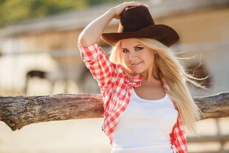 sexy young girl: Молодая женщина с длинными светлыми волосами, большой черной ковбойской шляпе, фланелевую рубашку и джинсовые шорты синие проводит время в летнее время на ранчо, стоя рядом с деревянным забором на фоне летней зелени