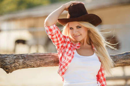 sexy cowboy: Young woman with long blonde hair, a big black cowboy hat, flannel shirt and denim shorts blue spends time in the summer at the ranch, standing near a wooden fence on the background of summer greenery