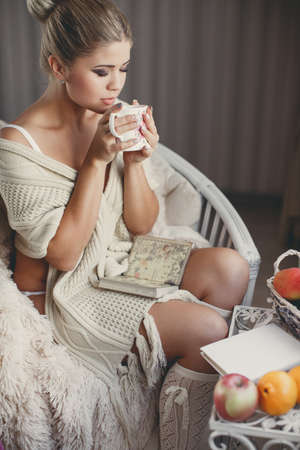 comfortable chair: Beautiful young woman with blonde hair gathered at the nape, fashion makeup, on the shoulders is a white knitted scarf, sitting on a comfortable chair, covered with beige blanket, holding a Cup of hot tea Stock Photo
