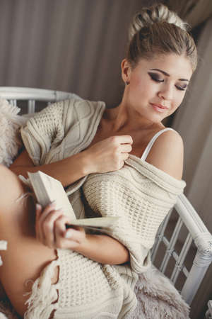 comfortable chair: Beautiful young woman with blond hair gathered at the nape, fashion makeup, on the shoulders of a white knitted scarf, sitting on a comfortable chair, covered with beige blanket in the hands holding an open book