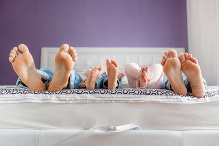 baby diaper: Feet of parents and children lying on the bed.Father, mother, son and daughter relaxing together lying on a white bed in purple bedroom, pink feet of the parents and children who watch TV lying on the bed four Stock Photo