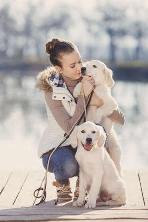 gray eyes: Beautiful girl with pets near the lake.Girl, brunette with gray eyes, hair pulled back, dressed in a brown sweater and blue jeans, spending time outdoors in the spring near a quiet lake with her two beloved dogs, breed Golden Retriever
