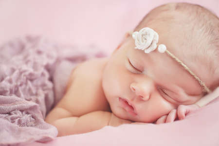 Close-up portrait of a beautiful sleeping baby.Happy carefree sleep little baby with wreath on head in warm pink bed, the child was put under the cheek stick, pink soft skin and fluffy hair, covered with a pink blanket Stock Photo