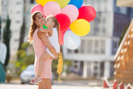 children celebration: Happy family, mother is a brunette with long curly hair and brown eyes, dressed in a pink dress and little daughter girl, brunette, dressed in a white dress and sandals, spend time together, walking outside in the summer with colorful balloons