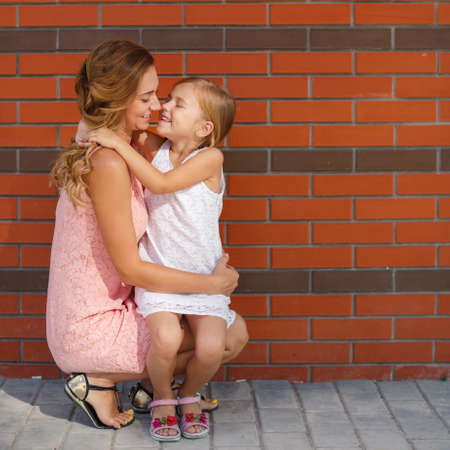 Happy family, mother is a brunette with long curly hair and brown eyes, dressed in a pink dress and little daughter girl, brunette, dressed in a white dress and sandals, spend time together, walking outside in the summer Stock Photo