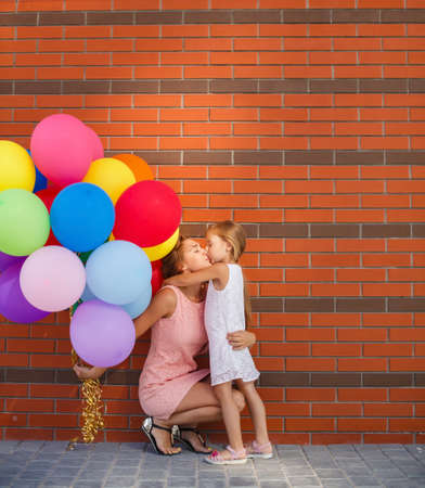 happy family nature: Happy family, mother is a brunette with long curly hair and brown eyes, dressed in a pink dress and little daughter girl, brunette, dressed in a white dress and sandals, spend time together, walking outside in the summer with colorful balloons