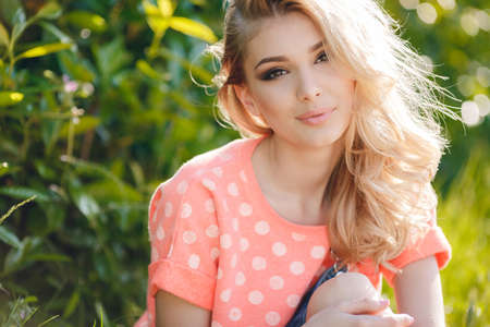 beautiful blonde girl with green eyes: Summer portrait of a beautiful woman.Very beautiful blonde girl with big brown eyes, bushy long hair, dressed in a pink T-shirt with white polka dots and denim overalls in dark blue, green park resting in a sunny summer day