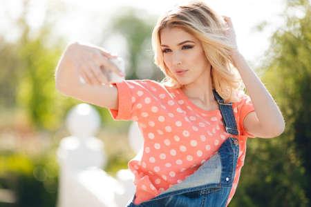 Very beautiful blonde with big brown eyes, thick long hair, dressed in a pink t-shirt with white polka dots and denim dark blue jumpsuit, spends his time in summer Park taking selfie on smartphone Stock Photo
