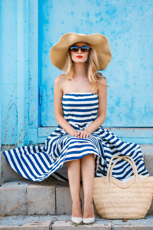 Fashion portrait. Smiling blonde woman in fashionable look. Sea style. On blue background. Style and hot girl outdoor. Woman in sun glasses and straw hat. Fashion.