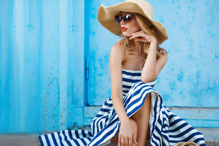 Woman portrait on blue background, sitting on the steps in a nice big straw hat and sun glasses, red lipstick and beautiful white teeth, with long blonde hair in a long striped dress with bare shoulders portrait of a model in the resort